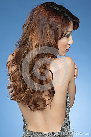 Back view of young woman over colored background