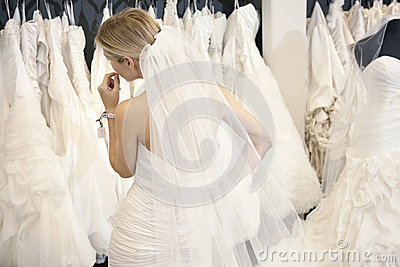 Back view of a young woman in wedding dress looking at bridal gowns on display in boutique