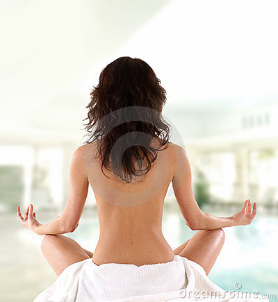 Back of a young and fit meditating brunette