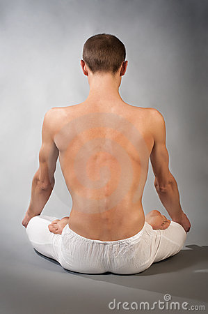 Back of young man in yoga position