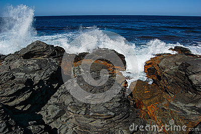 Blue waves crashing near a rocky shore