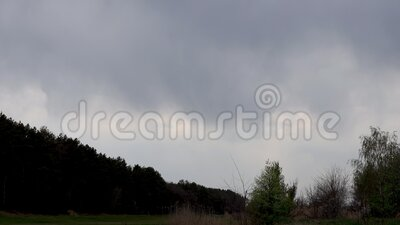 Background of dark clouds before a thunderstorm over spring fields and forest. Time lapse stock footage