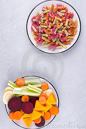 Free Background Of Bright Colorful Dry Pasta Made From Vegetables And Its Natural Vegetable Dyes Celery, Beet, Carrot, Pumpkin, Parsnip Stock Image - 113568981