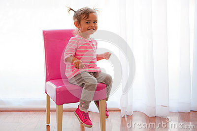 Backlit toddler girl on pink chair