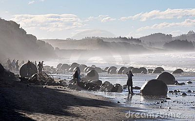 Backlit Tourists at Moeraki Boulders, New Zealand Editorial Photo