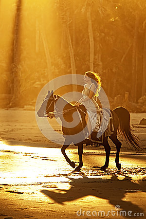 Backlit woman riding horse on beach