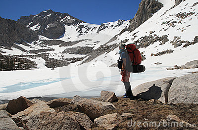 Backpacker by frozen lake
