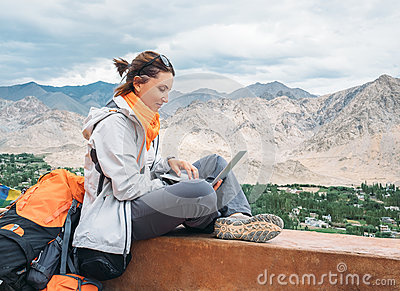 Backpacker with laptop sits on the top view point under mountain Stock Photo