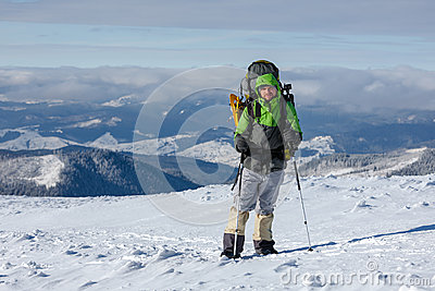 Backpacker man is posing in winter mountains Stock Photo