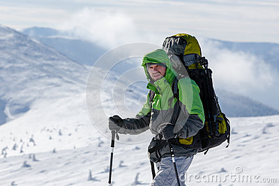 Backpacker man walking in winter mountains on sunny day Stock Photo