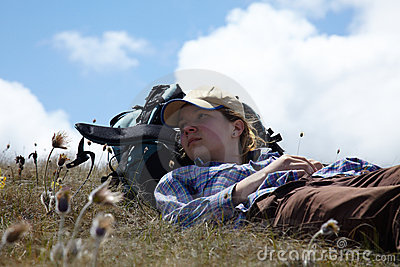 Backpacker relahing on a meadow