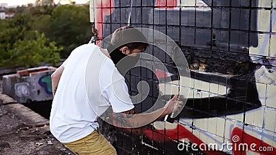 Backside Ansicht eines jungen Kaukasier-Typen in der Freizeitbekleidung kreativ arbeitet mit einer Außenwand, gegossene Wand, stock video