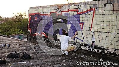 Backside Ansicht eines jungen Kaukasier-Typen in der Freizeitbekleidung kreativ arbeitet mit einer Außenwand, gegossene Wand, stock video footage