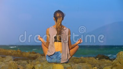 slim girl with ponytail sits in lotus pose at ocean stock