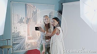 Backstage del servizio fotografico: modello nero attraente per il selfie con un artista di trucco stock footage