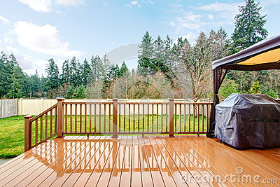 Backyard with wet deck, grill and fence.