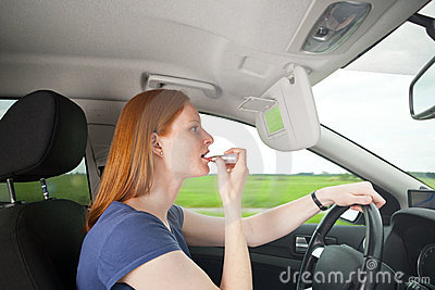 A bad driver - woman putting on makeup