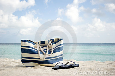 Bag and flip-flops on the beach