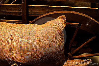 Bag of goods lay against the wooden wheel