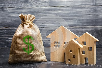 A bag with money and three houses. Concept of real estate acquisition and investment. Affordable cheap loan, mortgage. Taxes Stock Photo