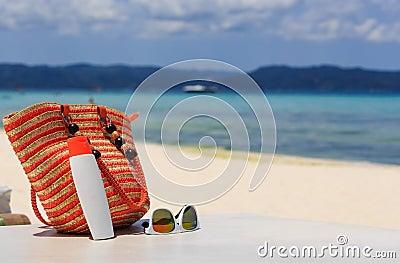 Bag, sun glasses and suncream on tropical beach