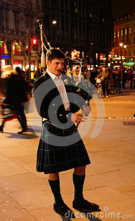 Bagpiper blowing his pipes Editorial Stock Photo