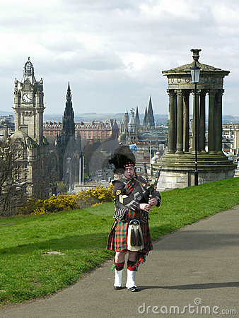 Bagpiper in Edinburgh, over cityscape Redactionele Afbeelding