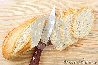 Baguette sliced on wooden board