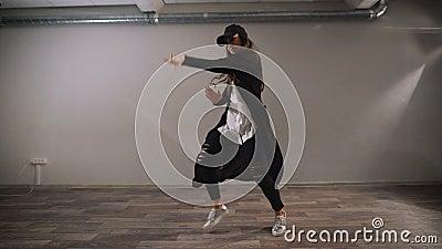 Bailarín de sexo femenino en la camisa blanca, pantalones negros y el casquillo negro mostrando el baile moderno del jazz-miedo e metrajes