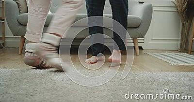 Baile casero de los pares del estilo en el primer de la sala de estar que captura las piernas metrajes