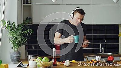 Baile feliz alegre del hombre y canto en cocina mientras que practica surf medios sociales en su smartphone en casa por la mañana metrajes