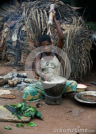 The Baka  woman pounds a flour in a mortar. Editorial Photography
