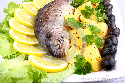 Baked fish with potatoes, black olives, lemon and salad