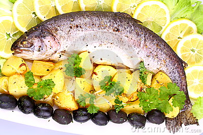 Baked fish with potatoes, black olives, salad and  lemon