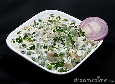 Baked vegetable in a white bowl with onion slice