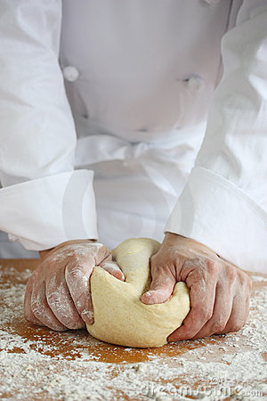 Baker making bread, kneading a dough
