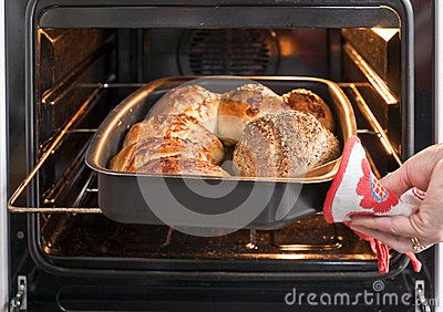 Baker s hand with bread in oven