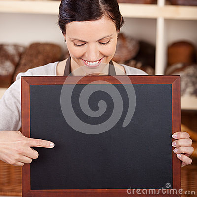 Bakery assistant pointing to a blank blackboard