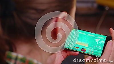 Bakre vy över kvinnor som håller telefon med diagram lager videofilmer