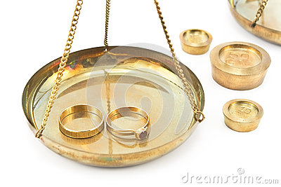 Balance scales with golden wedding rings