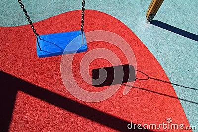 Balanço azul do parque ou campo de jogos vermelho das crianças do assoalho