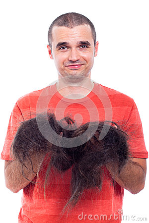 Bald man holding his long shaved hair