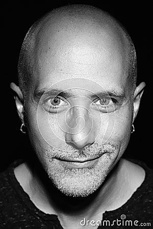 Bald man portrait half smile