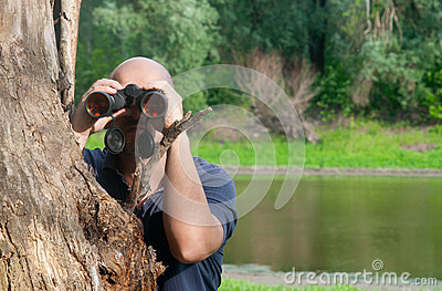 Bald man watching the nature through binoculars