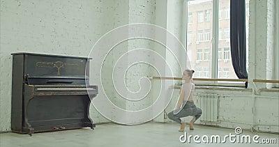 Baletniczy tancerz ćwiczy uroczystego plie przy barre zbiory