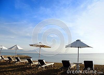 Bali beach resort scene with loungers