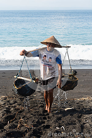 Traditional sea salt production on the volcanic black sand, Bali Editorial Photography