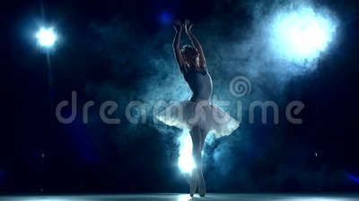Ballerina in the classroom on blue. slow motion. Graceful ballerina doing a workout in the classroom. Smoke, fog, silhouette. ballet dancer in white tutu, girl