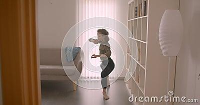 Ballerina di prima caucasica tenera che esegue ballo contemporaneo nella luce e nella stanza accogliente stock footage