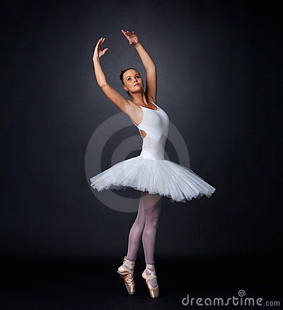 Ballerina performing against black background